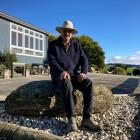 Farmer Peter McNab sits on one of the boulders being used as a garden ornament. PHOTO: MARY-JO...