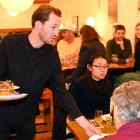 Everybody Eats founder Nick Loosley serves dinner at Kind Company on Friday night.