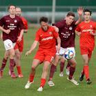 Caversham's Rhys Henderson (centre) and Dunedin Technical's Dominic Blake battle for possession...