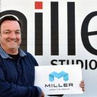 Managing director Keith Cooper holds the  logo for the rebranded Miller Creative Group. Photo by...
