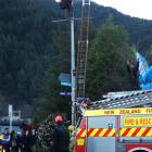 A paraglider pilot waits to be rescued from a streetlight pole in downtown Queenstown yesterday....