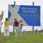 Swiss tourists take photographs next to a road that marks the England-Scotland border.