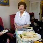 Joyce Myers (83) serves afternoon tea to Bell McGregor (99) to mark her retirement from Highview...