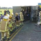 Members of the Kaitangata fire brigade pull a cow out of a trailer which rolled on to its side on...