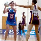Steel shooter Megan Dehn shapes to pass the ball past Queensland Firebirds defender Peta Stephens...