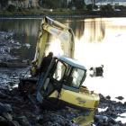 A digger is stuck in the mud at the Andersons Bay inlet yesterday.