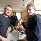 AgResearch scientist Scott Hardwick (left) hands Ikawai farmer Mark Caldwell phials of...