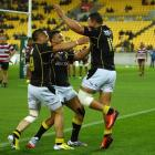 Alapati Leiua (right) of Wellington celebrates his try with teammates Frae Wilson (left) and Lima...