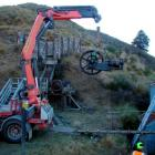 Contractor Charlie Skevington uses a hydraulic lifting arm to lower a 109-year-old Tangye stamper...
