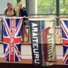 German backpackers Naomi Eul (left) and Alina Probst admire historic flags on display at the...