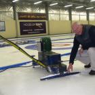 Maniototo Curling International Inc manager Bruce McCormick clears ice from the machine used to...
