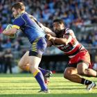 Otago's Michael Collins (L) is tackled by Counties Manukau first five Ahsee Tuala during the...
