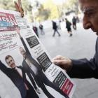 A man studies a newspaper displayed on a stand, in Tbilisi, with images of Georgian Prime...