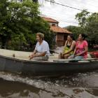 People travel on a boat near flood-affected houses in Asuncion. REUTERS/Jorge Adorno