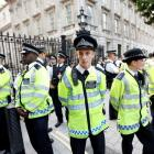 Police guard the entrance to Downing Street during a rally in central London against the proposed...