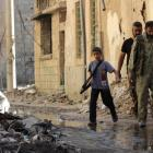 A boy carries a weapon as he walks with members of the Free Syrian Army on a damaged street...