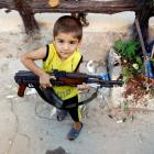 A boy plays with an AK-47 rifle owned by his father in Azaz, 47km north of Aleppo in Syria. The...
