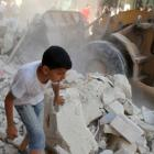 A boy walks beside a bulldozer while people look for survivors following what activists say was...