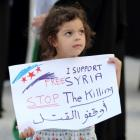 A child holds a banner as she participates in an anti-Syria regime protest held by Bahrainis at...