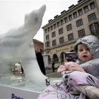 A child is seen next to a melting ice statue of a polar bear in the centre of Copenhagen, Denmark...