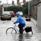 A commuter makes his way to work through flooded streets in Dublin. Photo: REUTERS/Cathal McNaughton