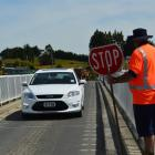 A contractor controls traffic on the Clydevale bridge  as  preparations are made to  repair the...