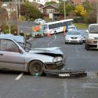 A contractor inspects the scene of a car crash in Highcliff Rd, Dunedin, yesterday. Photo:...