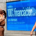 A couple kiss next to a sign that advertises credit facilities at a commercial quarter in central...
