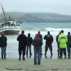 A crowd gathers on the Curio Bay beach yesterday to watch the stranded fishing boat Silver Fern...