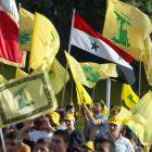 A crowd watches Lebanon's Hezbollah leader Sayyed Hassan Nasrallah as he appears on a screen...