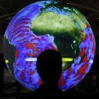 A delegate looks at a giant globe which displays the warming of the world's ocean in the US...