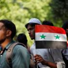 A demonstrator holds the Syrian flag during a protest in New Delhi, India, against potential US...