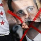 A demonstrator punches through a portrait of Syria's President Bashar al-Assad during a protest...