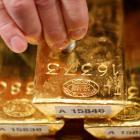 A Deutsche Bundesbank worker tests a gold bar with an ultrasonic appliance during a news...