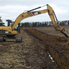 A digger lays the first pipe in an extension to the North Otago Irrigation Company's scheme,  on...