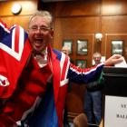 A Falkland Islander gestures as he casts his vote at the Town Hall polling station in Stanley....