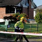 A firefighter outside the Auckland home where four children died. Another three people are in a...