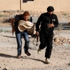 A Free Syrian Army fighter carries bread as he runs with a fellow fighter to avoid snipers loyal...