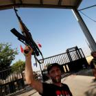 A Free Syrian Army soldier raises his rifle at the Bab Al-Salam border crossing to Turkey....