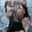 A garbage bag hangs from a portrait of Muammar Gaddafi in Tripoli.  (REUTERS/Zohra Bensemra)