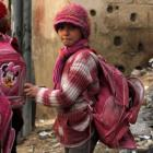 A girl carries a torn school bag as she stands in front of debris outside a school in the Duma...