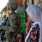 A girl stands next to a United States soldier in Jalalabad, Afghanistan this week. Photo: Reuters.