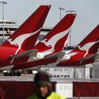 A ground staff worker walks in front of Qantas planes at Sydney's domestic airport.   REUTERS...