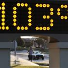 A jogger runs past sprinklers and a time and temperature sign in Lawrence, Kansas. (AP Photo...