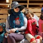 A Jordanian UN volunteer sits with a Syrian refugee child at the Al Zaatri refugee camp in the...