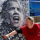 A local artist named 'O' shows off his lithograph featuring President Barack Obama for sale at...