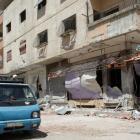 A lorry drives past a damaged building at Moadamya area near Damascus. REUTERS/Khaled al-Hariri
