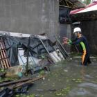 A man clears debris near his house flooded by Typhoon Saola in Wujie in Ilan County, Taiwan....