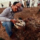 A man collects human remains at the site of a mass grave in Tripoli said by authorites to contain...