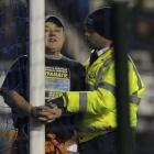 A man handcuffs himself to the goal post during the English Premier League soccer match between...